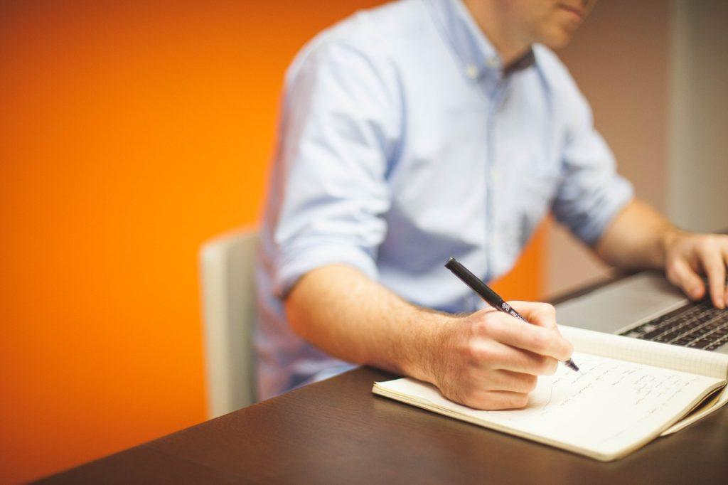 Person mit Stift, schreibend