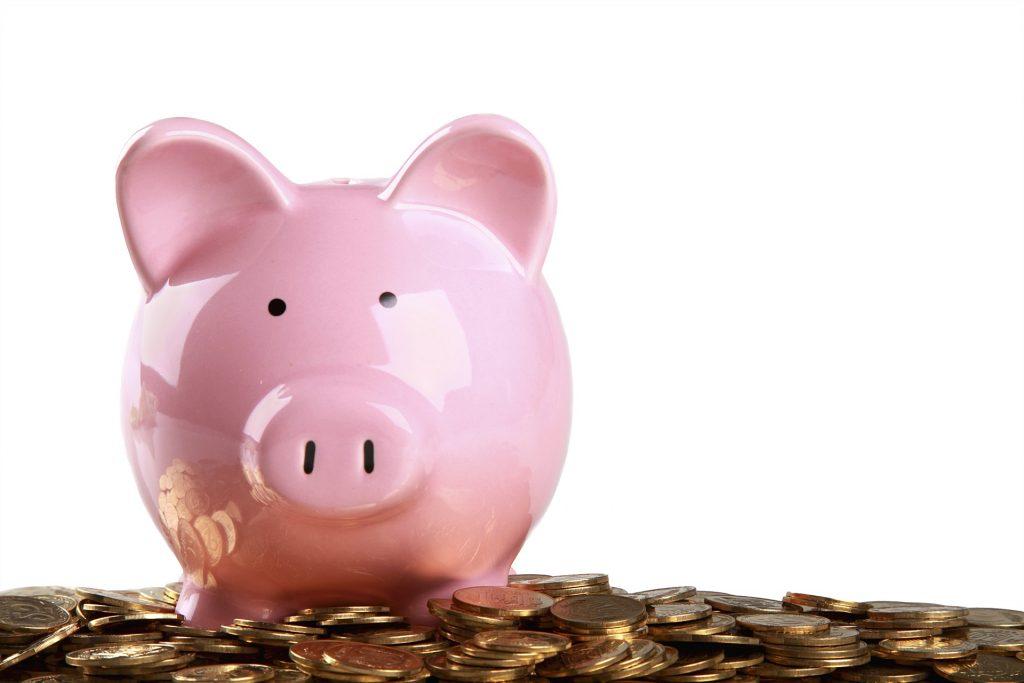 Sparschwein sitzt auf Münzen